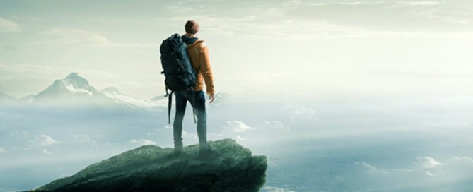 Man overlooking clouds from mountain